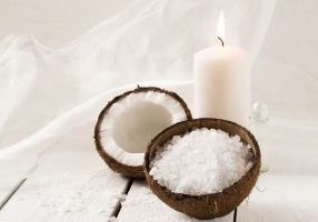 47037870 - coconut spa and wellness setting (coconut, sea salt, scented candle with coconut, coconut oil) on a white background